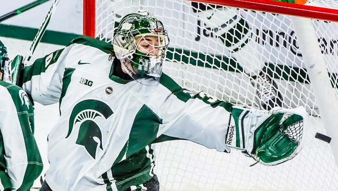 A Minnesota shot on goal flies by just past the outstretched glove of Michigan State goalie Jake Hildebrand on Dec. 5, 2014.