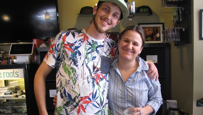 At the downtown Denver Native Roots Apothecary, assistant manager Michael Pyatt, left, poses with a fellow employee. The medical marijuana dispensary recently began selling recreational weed and is getting 150 to 200 clients a day, he says. Popular strains include Dark Dream and Dead Man.