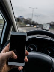 Arizona passes ban on cellphone use while driving.