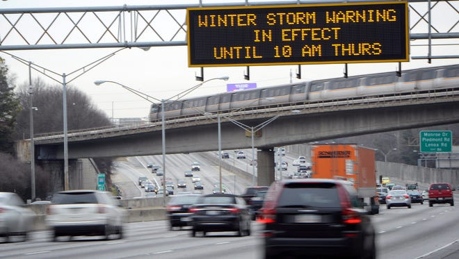 Drivers on Interstate 75 and a MARTA commuter train make their way north out of the city as a winter weather warning is displayed in Atlanta on Feb. 25, 2015.