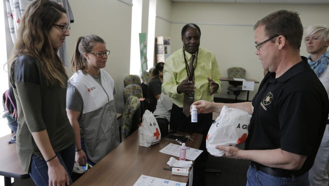 Rick Leib of Oshkosh North Communities looks at what the Red Cross would give to refugees during a simulation of refugee training at UW-Oshkosh.