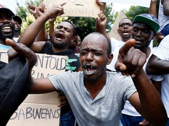 Protesters sing during a demonstration of Zimbabwean citizens outside the Zimbabwean Embassy in Pretoria on Jan. 16, 2019, following the announcement of a petrol price hike in Zimbabwe and the recent shut down of mobile phone networks and internet services. Three people were shot dead on Jan. 15 and many were injured when Zimbabwean security forces cracked down on protests triggered by the president's announcement that fuel would more than double in price as the country's economic crisis deepens.