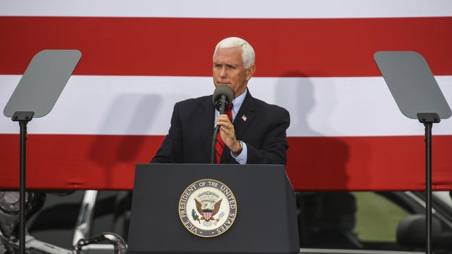 "Vice President Mike Pence takes the stage during a campaign rally at an AvFlight Hangar in Traverse City, Mich., Friday, Aug. 28, 2020. Pence, flanked by construction equipment and ""Make America Great Again"" banners, touted President Donald Trump's policy accomplishments Friday while urging Michigan voters to support his reelection. (Mike Krebs/Traverse City Record-Eagle via AP)/Traverse City Record-Eagle via AP)"