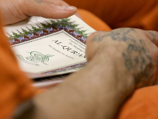 An inmate holds the Quran as he listens to Imam Mohammed