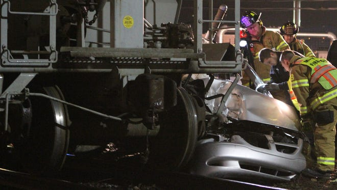 Emergency responders work on a car after it was struck by a freight train crossing Philadelphia Pike near the Pennsylvania state line shortly after 7 p.m. Saturday,