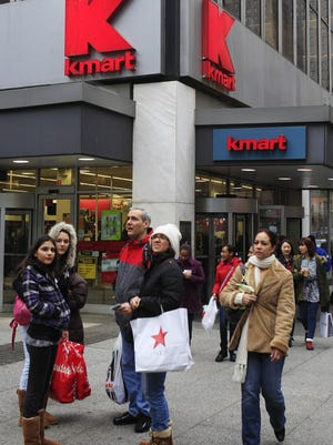 ORG XMIT: NYFF103 Pedestrians pass a Kmart location Tuesday, Dec. 27, 2011, in New York. Sears Holdings Corporation, the parent company of Sears and Kmart department stores, announced Tuesday morning that it will close 100 to 120 stores after a sluggish holiday season.(AP Photo/Frank Franklin II)