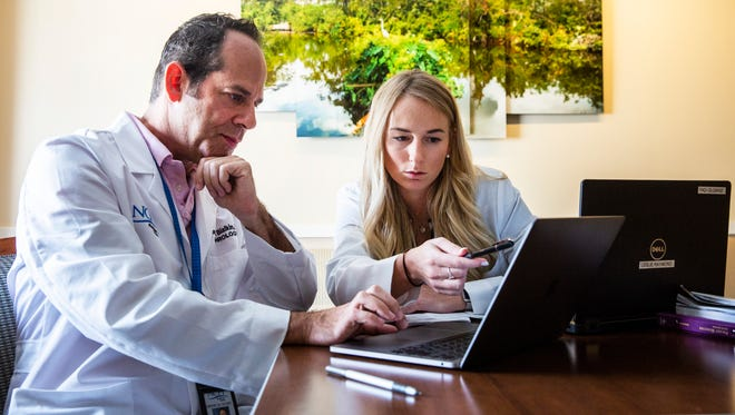Dr. Leslie Raymond a new resident physician, reviews patient information with her attending physician, Dr. Steven Bialkin, a nephrologist, during one of her rotations at NCH Baker Hospital Downtown on July 6, 2018. The NCH Healthcare System welcomed its second class of 12 physicians, including Raymond, on July 1 for its three-year internal medicine residency program.