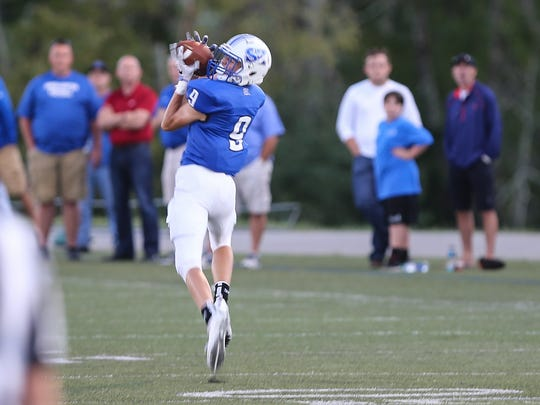 Simon Kenton's Fisher Hayden pulls in a pass on the way to a 77-yard touchdown during their game with Conner at Simon Kenton, Friday, September 2, 2016.