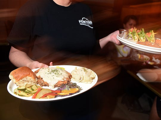 A server carries chicken fried chicken and tacos on Monday at Porter's Restaurant in Farmington.