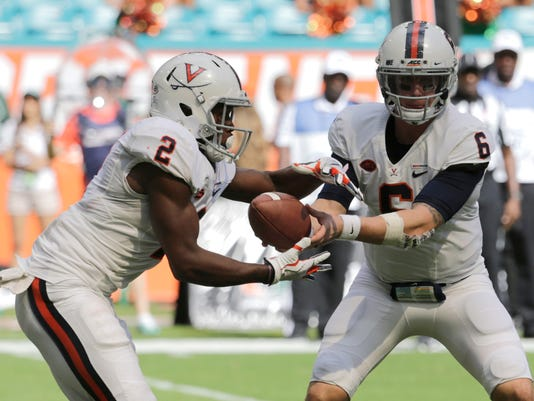 Virginia quarterback Kurt Benkert (6) hands off the football to wide receiver Joe Reed (2) during the first half of an NCAA college football game, Saturday, Nov. 18, 2017, in Miami Gardens, Fla. (AP Photo/Lynne Sladky)