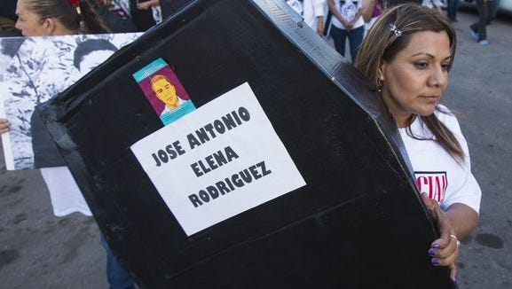 Araceli Rodríguez carries a makeshift coffin for her son during a march in Nogales, Sonora, Mexico.