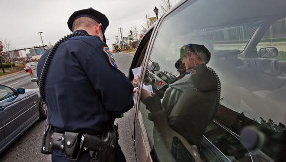 Wilmington Police Patrolman Jeff Dickerson, seen here in 2011, cites a motorist. State officials met Wednesday to figure out how to convince drivers to pay traffic fines.