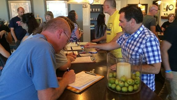Customers at Josiah's Coffeehouse in downtown Sioux Falls sign petitions to cap interest rates for payday lending in South Dakota.
