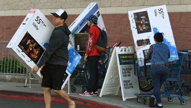 """Shoppers with their arms full walk to their cars during the """"Black Friday"""" sales at a Best Buy store in Culver City, Calif."""