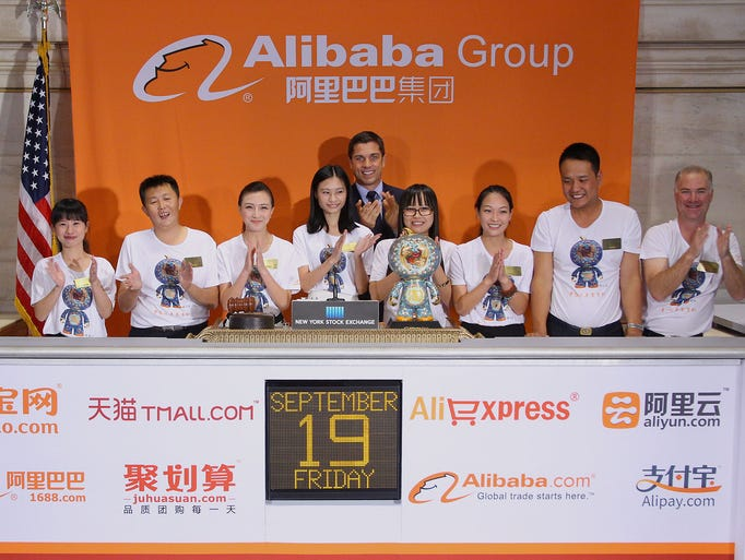 Representatives from Alibaba ring the opening bell as they launch their initial public offering of stock at the New York Stock Exchange.