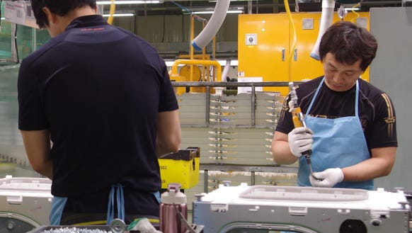 Workers assemble LG washing machines.