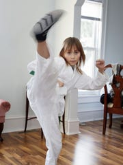 Makayla Zavrl, 9, demonstrates her karate skills in her home Tuesday March 8, 2016 in Sheboygan.  Zavrl was bullied and her family took steps to help stop the problems.