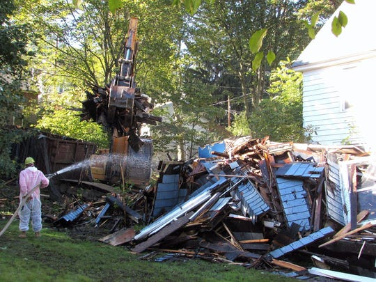 A crew from Swarthout Recycling demolishes an arson-damaged house on East Third Street in Corning.