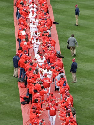 The Phillies are greeted by their fans as they walk from in from the outfield stands before their home opener on Friday.