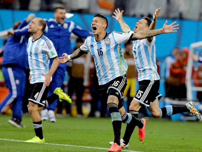 Argentina players react after Maxi Rodriguez scored the winning penalty.
