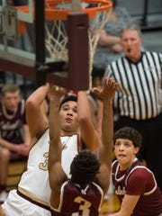 Webster County's Malachi Douglas (30) shoots over Henderson's Daymian Dixon (3) and Corey Stewart (2) during their game at Webster County High School last season.