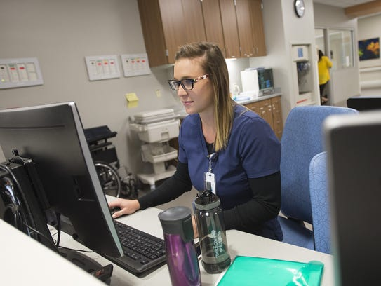 Registered Nurse Janna Roark works on a patient's chart