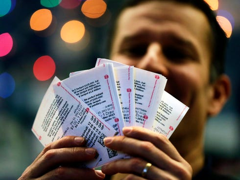 Chad Cuneo displays Mega Millions lottery tickets he purchased at a newsstand Friday in Philadelphia.