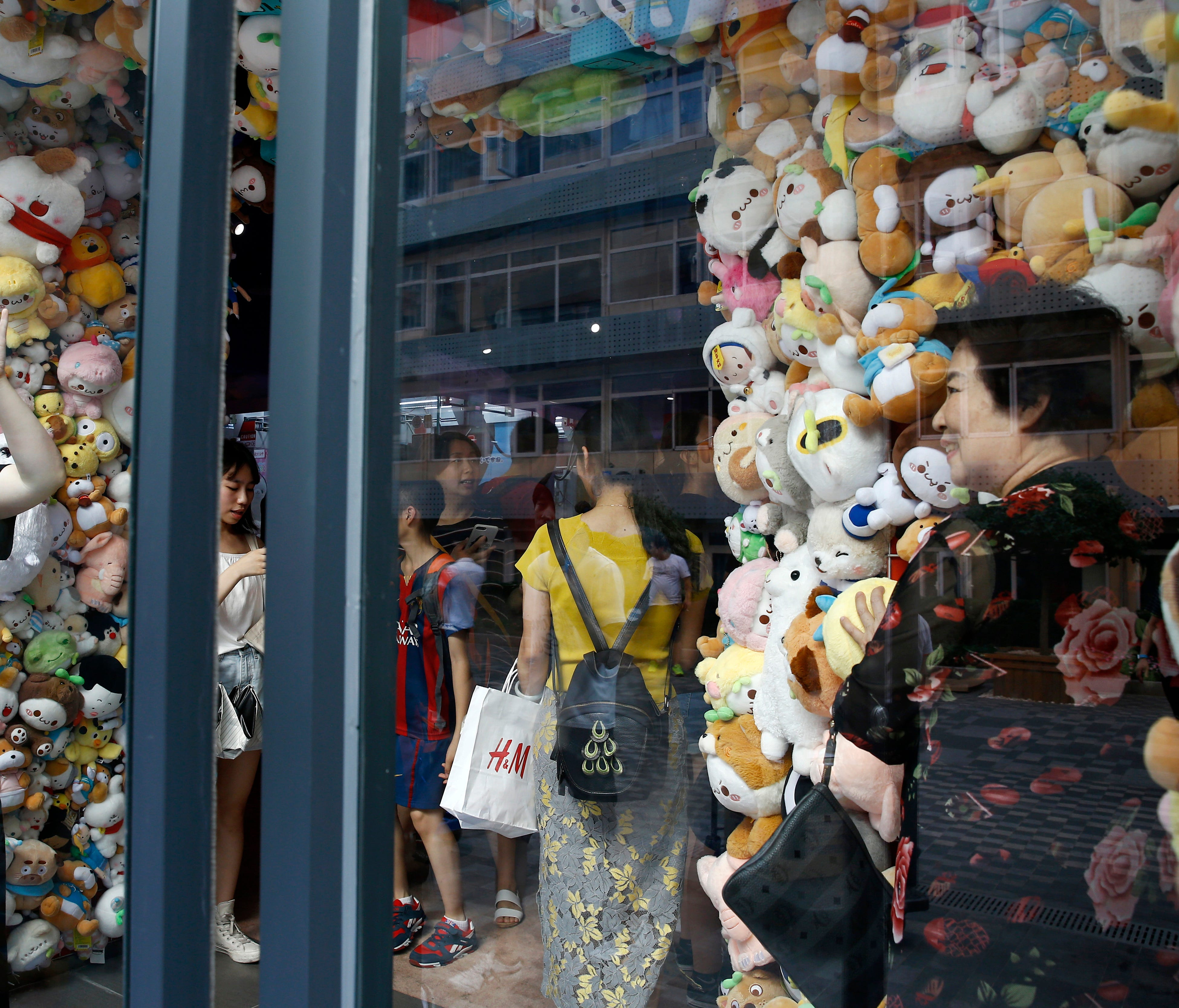 In this Sunday, July 15, 2018, photo, women take souvenir photos with soft toys on display at an arcade games shop in Beijing. China's economic growth slowed in the quarter ending in June, adding to challenges for Beijing amid a mounting tariff battl
