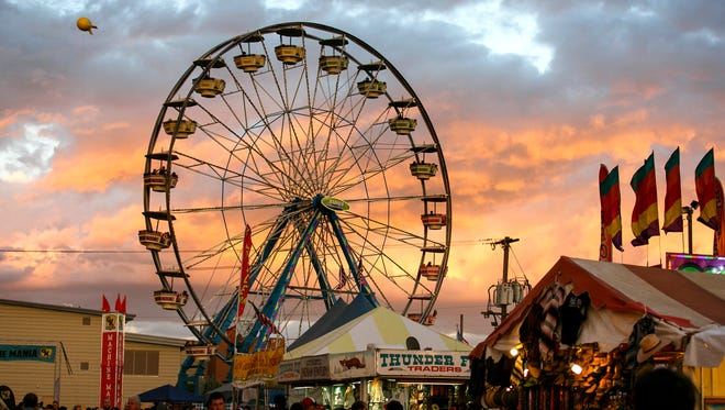 The sky turns orange behind the ferris wheel as the sun sets at the Oregon State Fair on Sunday, Sept. 4, 2016. The wheel rises 110 feet, and 6-8 people can fit in the open-air gondolas for a birds-eye view of the 185-acre fairgrounds.