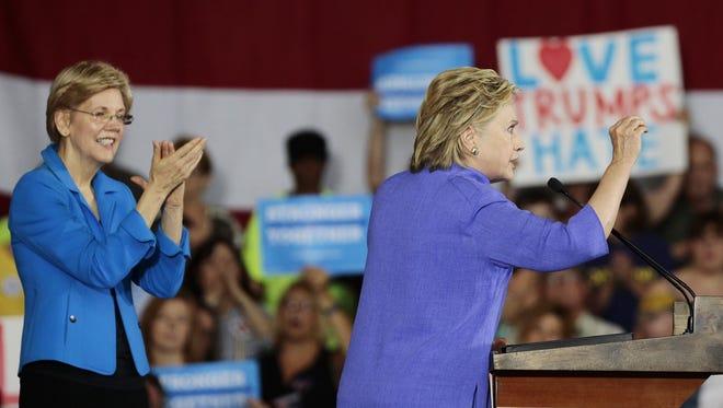 Hillary Clinton speaks to supporters gathered at Union Terminal in June as U.S. Sen. Elizabeth Warren applauds.