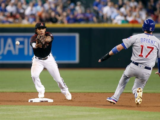 Arizona Diamondbacks shortstop Ketel Marte, left, cannot make the catch of a throw from Diamondbacks second baseman Brandon Drury to force out Chicago Cubs' Kris Bryant (17) on a ground ball hit by Cub's Anthony Rizzo during the first inning of a baseball game, Saturday, Aug. 12, 2017, in Phoenix. (AP Photo/Ralph Freso)