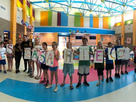 "Rodrigo Vásquez's students hold up signs that spell ""Quieres casarte conmigo"" (Will you marry me?)."