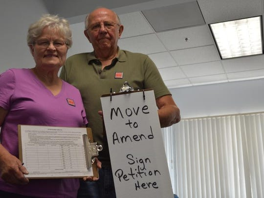 Rita and Milt Pachal pose with petition forms that seek an amendment to the Constitution. The revision looks to end corporate personhood and to eliminate monetary donations as a form of free speech.