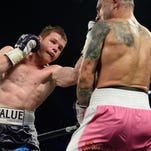 Canelo Alvarez (purple trunks) and Miguel Cotto (pink trunks) box during their WBC & Ring Magazine middleweight boxing title fight at Mandalay Bay Events Center.