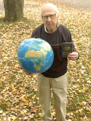 "Garry Davis of South Burlington considered himself a citizen of the world, shown in 2005 holding his world passport, and a globe with no political boundaries that he called ""the real world."""