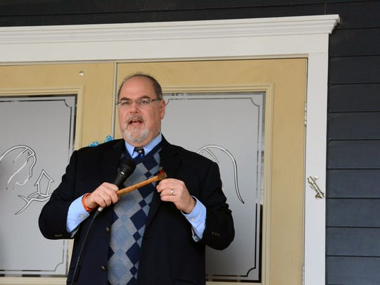 In this file photo, a rabbi addresses guests after placing a mezuzah (shown at right).
