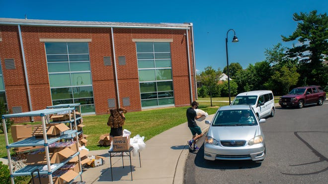 FILE: Cars line up during the meals distribution program Thursday at Mill Creek Elementary School in Bristol Township.