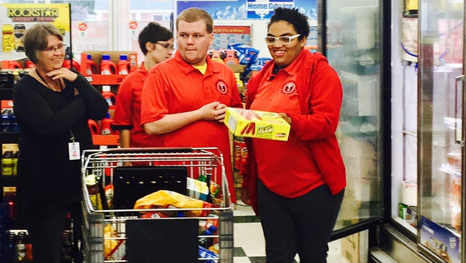 Kyle Neff, center, hands a box of popsicles to fellow Harding High School student Angie Booth at King Saver as part of a work study program for students with disabilities.