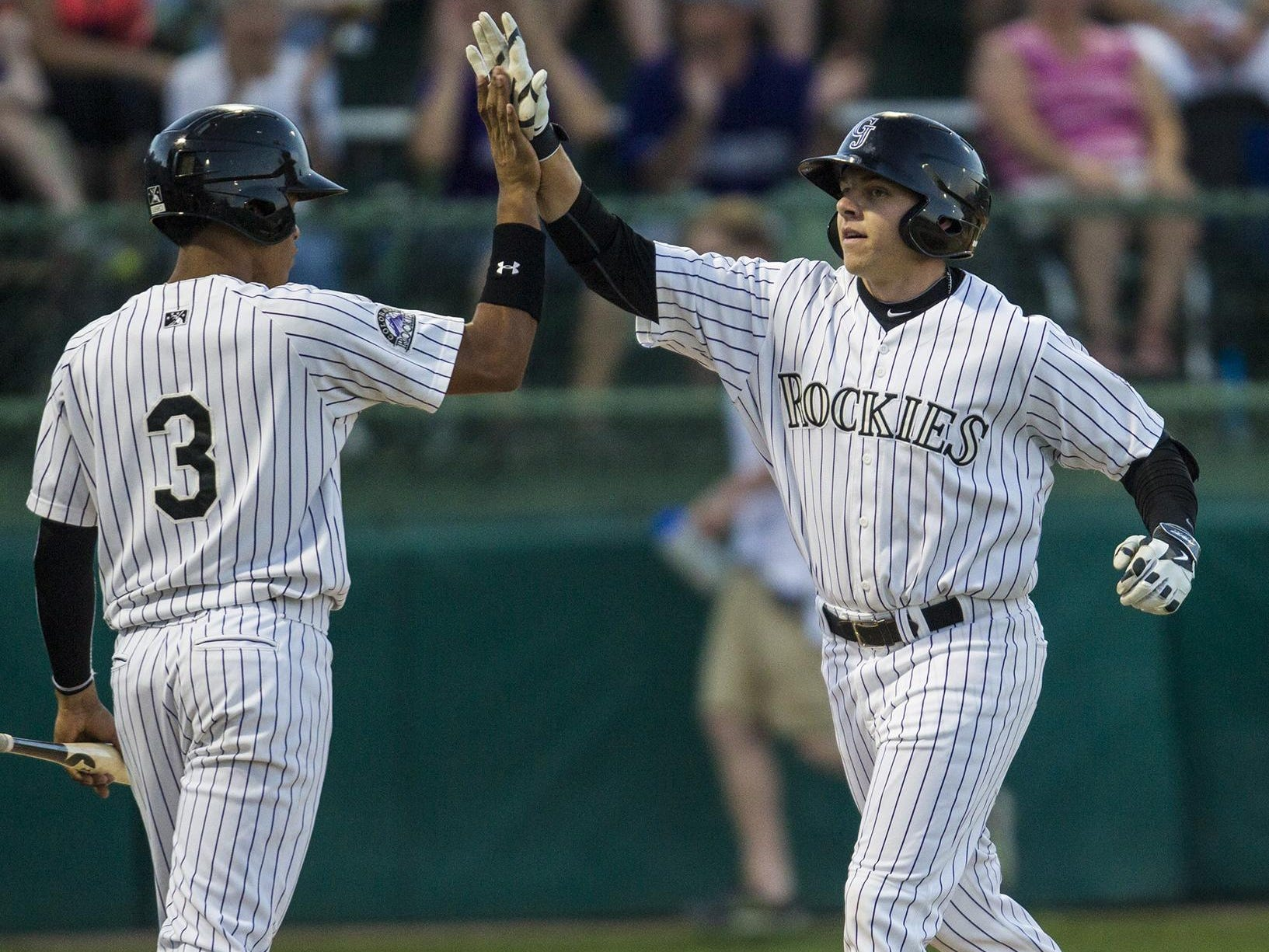 Rocky Mountain High School grad Cole Anderson, right, celebrates his first career hit, a home run, during the Grand Junction Rockies home opener Monday.