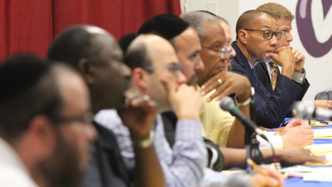 Dennis Walcott, 2nd from right, and members of the East Ramapo school board listen to residents speak at Chestnut Ridge Middle School on Aug. 18, 2015.