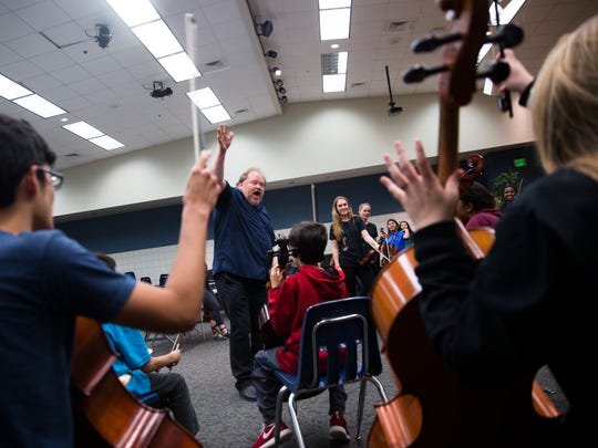 Dean Marshall, music director for Barrage 8, helps the cello section shout with enthusiasm during a rehearsal with Barrage 8, a professional string group, at Pine Ridge Middle School on Monday, February 13, 2017 in North Naples. The group will perform with students on Friday as a part of the master class  presented by the Naples Music Club.