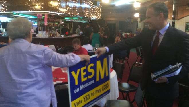 Aaron Starr, right, hands a supporter a sign supporting Measure M ahead of the 2016 elections. Starr authored Measure M, which the city of Oxnard challenged in court and lost.