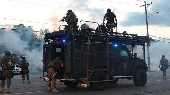 Tactical officers fire tear gas at protesters Aug. 11 in Ferguson, Mo.