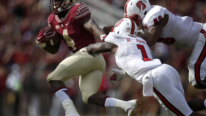 FSU's Dalvin Cook breaks away from NC State's Hakim Jones (1) and Bryan Smith for a long touchdown run during a game earlier this season.