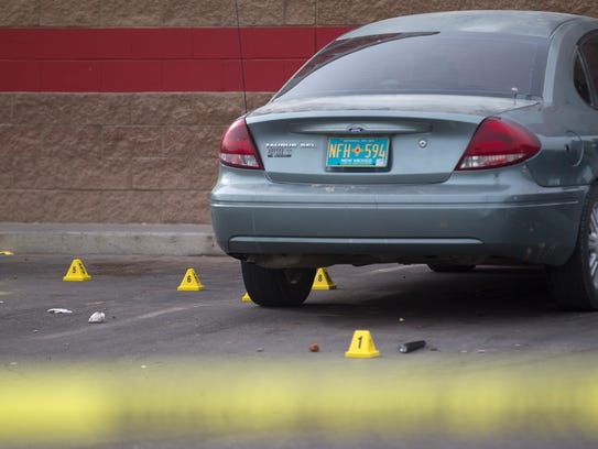 Evidence markers dot the parking lot of the Laundratopia location at 101 Gooding Lane in Farmington on Friday after a stabbing left a man in critical condition.