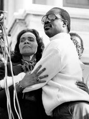 Coretta Scott King, widow of the Rev. Martin Luther King Jr., embraces singer Stevie Wonder during a celebration on the steps of the U.S. Capitol Building in Washington, D.C., Nov. 3, 1983.