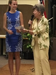 Sydney Towle receives a scholarship from Marty Neal,