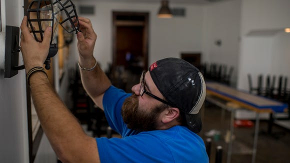 Collin Cormier, owner and chef at Pop's Po-Boys, places a light fixture onto the wall while preparing the restaurant for its upcoming grand opening in downtown Lafayette, La., Monday, March 16, 2015.
