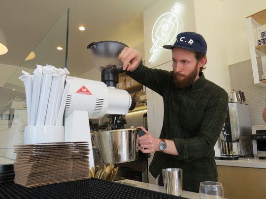 Blake Ulrich grinds beans behind the counter at Prospect Coffee Roasters, the coffee bar he and brother Derek Ulrich opened this week in downtown Ventura.