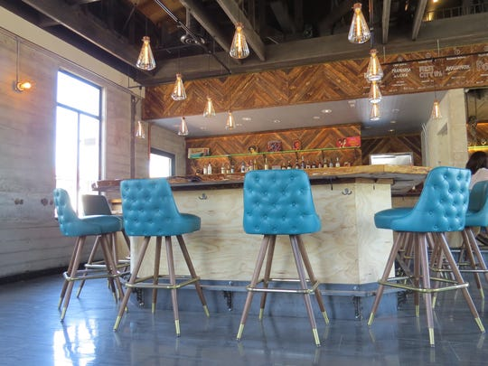 """Steakhouse chairs"" with diamond tufting ring the bar at Fluid State Beer Garden in downtown Ventura."